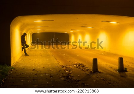 Intimidating man in a tunnel on a foggy night.