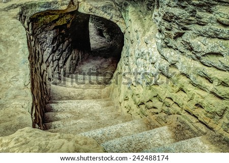 Into The Darkness. Ancient stone stairway leads into an unknown darkness. - stock photo