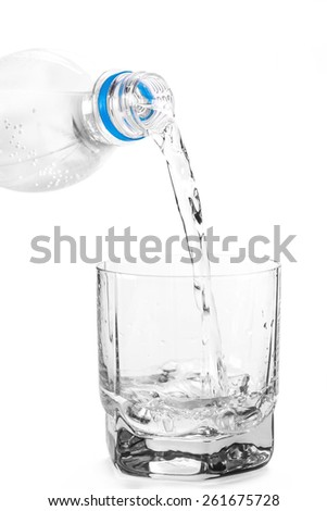 into the glass water is poured on white isolated background - stock photo