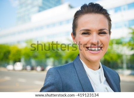 Into the ultra-modern business trends. Portrait of smiling business woman in modern office district