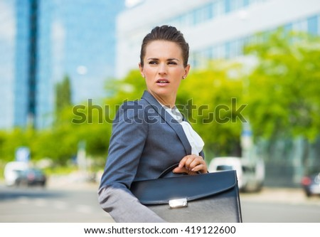 Into the ultra-modern business trends. Portrait of worried business woman with briefcase in modern office district