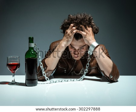 Intoxicated man sitting alone / photo of youth addicted to alcohol, alcoholism concept, social problem - stock photo