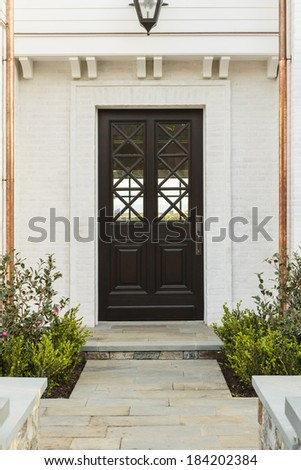 Intricate design on a wooden front door to a family home. Door features criss-cross glass patterns. House is whitewashed brick. Also seen is the stone walkway, light fixture; and copper drain pipes.