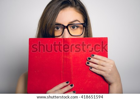 introvert beautiful girl hiding behind the book, in a yellow dress, closeup isolated on white background