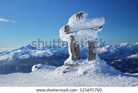 Inukshuk at the summit of Whistler Mountain peak on a sunny winter's day - stock photo