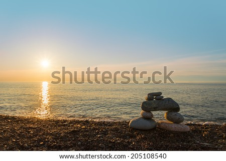 Inukshuk stones on ocean shore - stock photo