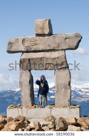 inukshuk with two children - traditional inuit symbol for 'the way' - stock photo