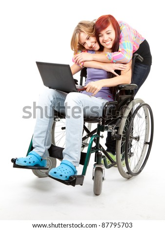 invalid girl on the wheelchair with laptop and her friend