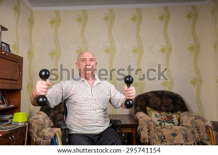 Invalid old man doing exercises with dumbbells - stock photo