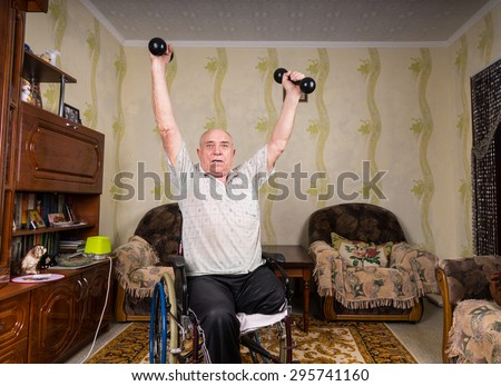 Invalid old man puts his hands up with dumbbells - stock photo