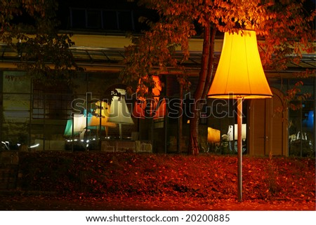 Inventive street lamp illuminating parking lot with reflecton in window - stock photo