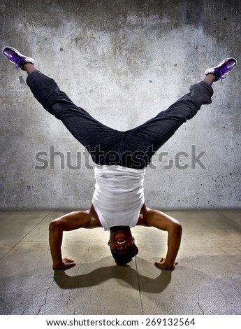 Inverted black breakdancer doing a headstand or handstand or urban yoga.  The concrete floor and background gives the image an urban setting. - stock photo