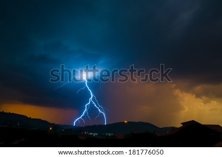Inverted Y shape lightning in thunderstorm on ridge and the sun setting in the backgorund - stock photo