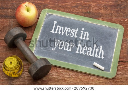 Invest in your health -  slate blackboard sign against weathered red painted barn wood with a dumbbell, apple and tape measure - stock photo