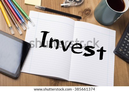 Invest - Note Pad With Text On Wooden Table - with office  tools - stock photo