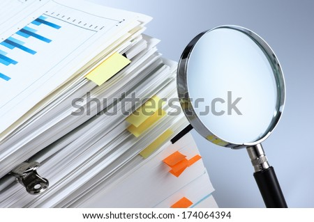 Investigate and analyze. Scanning business documents. Magnifying glass and stack of documents.  - stock photo