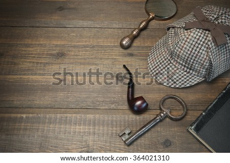 Investigation Concept. Private Detective Tools On The Wood Table Background. Deerstalker Cap, Old Key  And Book, Tobacco  Pipe, Vintage Magnifying Glass. Overhead View - stock photo