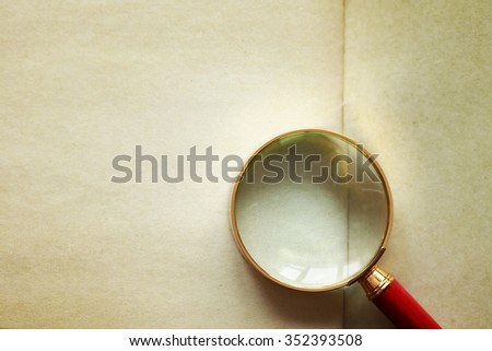 Investigation symbol. Magnifying glass on vintage paper background - stock photo