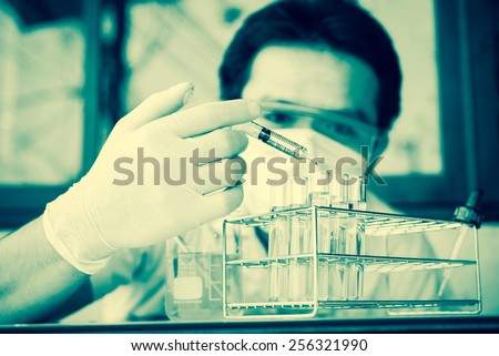 Investigator checking test tubes. Man wears protective goggles ; vintage filtered style - stock photo