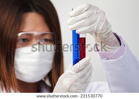 Investigator checking test tubes, Woman wears protective goggles. - stock photo