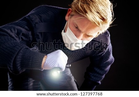Investigator holding a flashlight searching for evidence - stock photo
