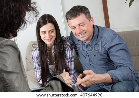 Investment adviser giving a presentation to a friendly smiling young couple - stock photo
