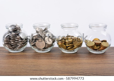 Investment Concept. Coins in bottle on the wooden table.