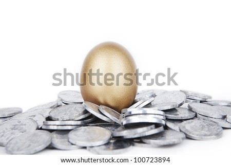 Investment concept: golden egg with coins isolated on white - stock photo