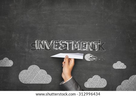 Investment concept on black blackboard with businessman hand holding paper plane - stock photo