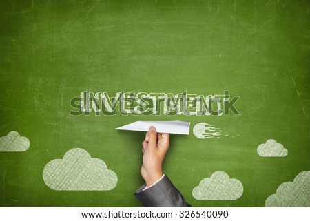 Investment concept on green blackboard with businessman hand holding paper plane - stock photo