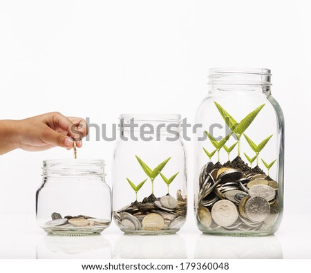 Investment growth concept,Hand putting Golden coins and seed in clear jar over white background - stock photo