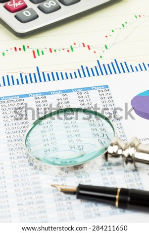 Investment report with magnifier, pen, and calculator
