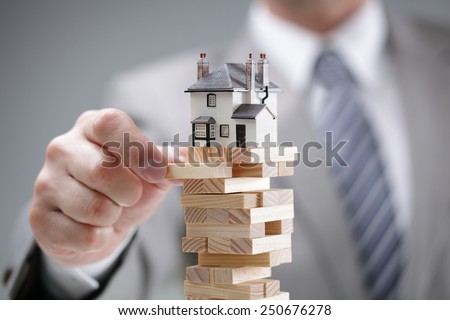 Investment risk and uncertainty in the real estate housing market - stock photo