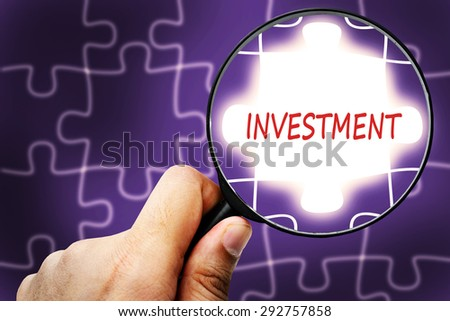INVESTMENT word. Magnifier and puzzles. - stock photo