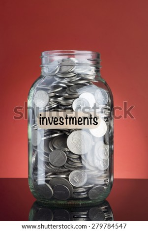 Investments Concept with money jar and coins on red background