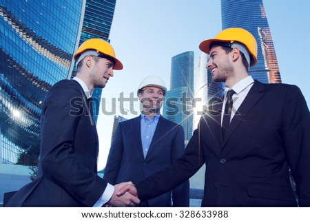 Investor and contractor shaking hands, view from below - stock photo