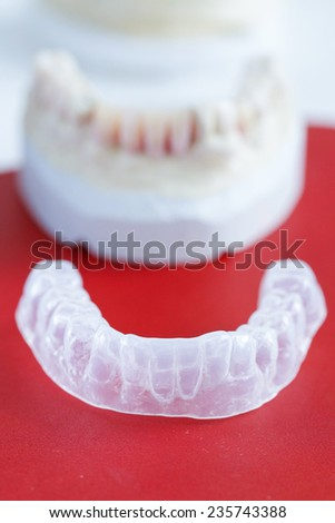 Invisalign, invisible plastic teeth aligner with dental plaster mold in the background - stock photo