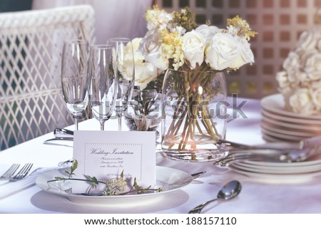 Invitation card on outdoor wedding table - stock photo