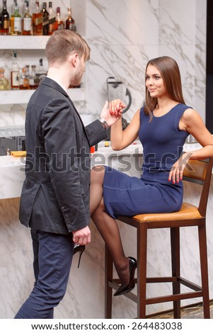 Invitation to dance. Young man inviting his girlfriend to dance while she is sitting on the chair at the bar counter - stock photo
