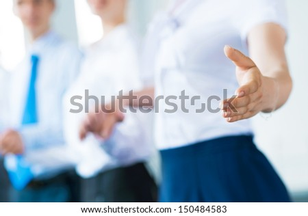 invitation to the team, business woman holds out her hand, her face a number of young businessmen