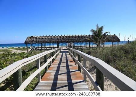 Inviting boardwalk to the ocean and a thatched roof chickee for shade - stock photo