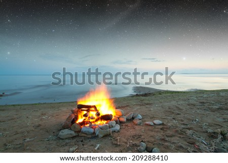 Inviting campfire on the beach during the summer. Elements of this image furnished by NASA - stock photo