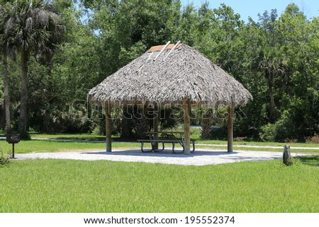 Inviting chickee thatched roof hut with picnic table, ready for a family gathering - stock photo