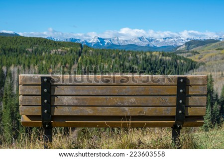Inviting empty bench overlooking a beautiful valley with snow capped mountains - stock photo