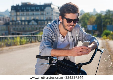Inviting friend for a ride. Handsome young smiling man leaning at his bicycle and looking at his mobile phone while standing outdoors  - stock photo