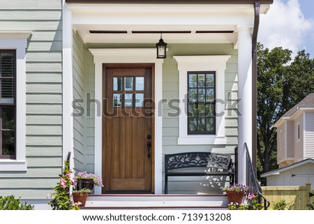 Inviting front porch with a brown front door