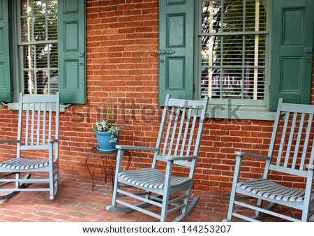 Inviting Front Porch With Brick Wall And Floor Warm Green Shutters And Trio Of Rocking