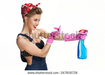Inviting housewife wearing pink rubber protective gloves holding spray / young beautiful American pin-up girl isolated on white background. Cleaning service concept - stock photo