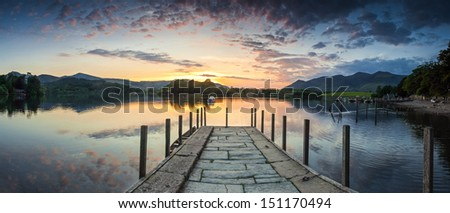 Inviting jetty leading to a dramatic sunset reflected in a perfectly still Derwent Water, Lake District, UK. - stock photo