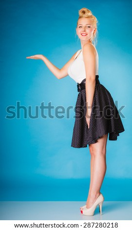 Inviting, showing and sharing concept. Pin up retro girl style. Blonde young full length woman with hand invitation gesture or copy space for text product on blue background in studio. - stock photo